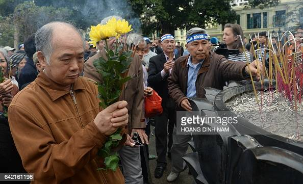 A Vietnamese veteran prays as people place incense sticks during a small rally marking the 38th anniversary of the Chinese war border against Vietnam...