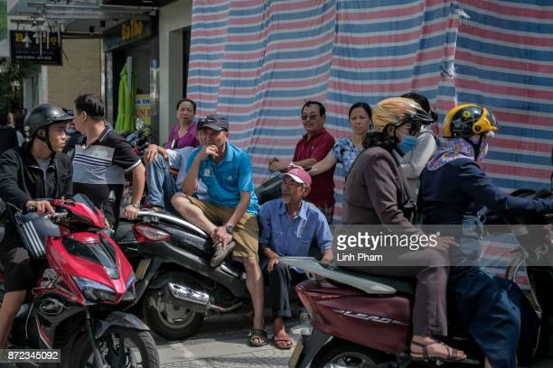 Vietnamese wait along the streets as the convoy transporting US President Donald Trump passes by on Nguyen Van Linh Road on November 10 2017 in...
