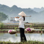 Vietnamese woman carrying baskets of flowers