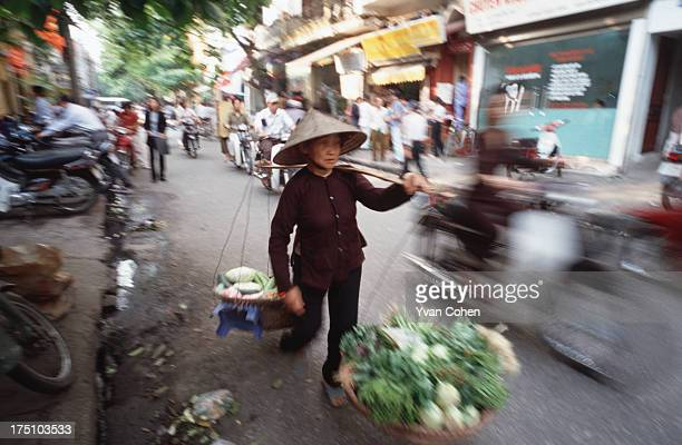 Vietnamese woman carrying two baskets in the streets of Hanoi