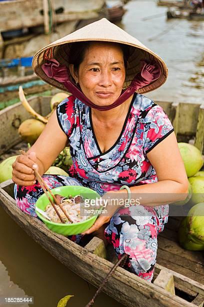Vietnamese woman eating Pho - noodle soup on floating market