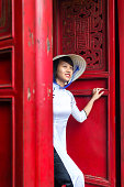 Vietnamese woman in ao dai dress near red door