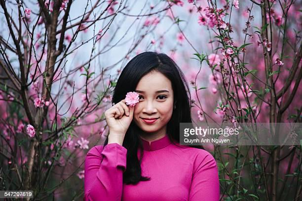 Vietnamese woman in peach apricot blossom garden