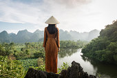Vietnamese woman on hilltop in front of mountains