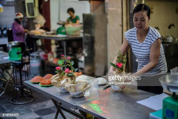 A Vietnamese woman organizes a table with cooked Chickens for sale that are adorned by pink roses in front of a food shop in the old quarters in...