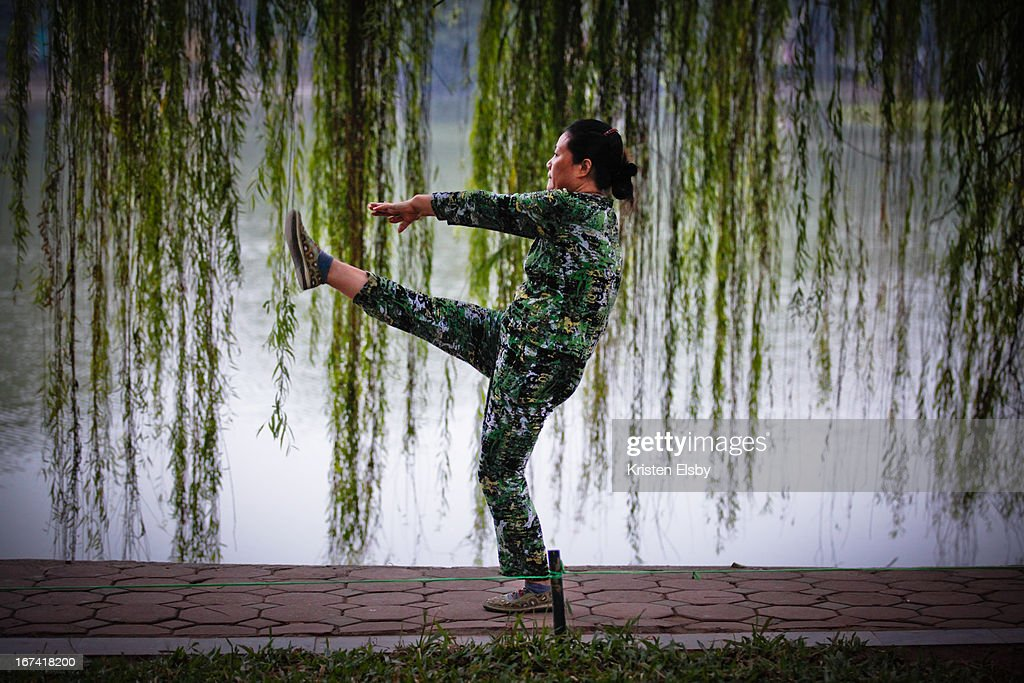 Vietnamese woman performs early morning calisthenics at Hoan Kiem Lake, central Hanoi, a daily routine carried out alongside many thousands of other locals.