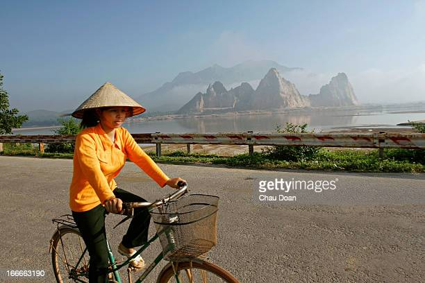Vietnamese woman rides a bicycle on highway