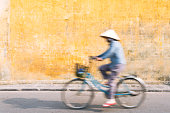 Vietnamese woman riding a bicycle in Hoi An