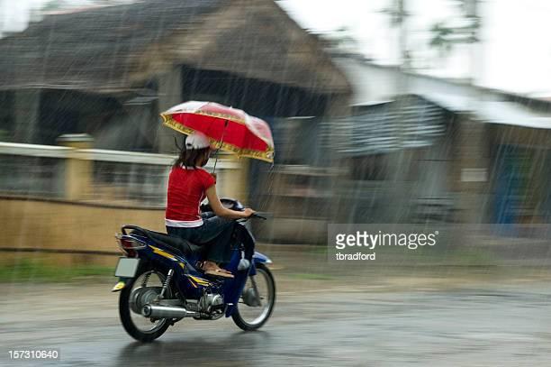 Jeune femme la moto tout en tenant un parapluie