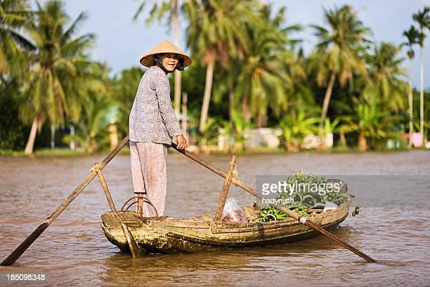Vietnamese woman rowing  boat in the Mekong River Delta, Vietnam