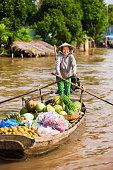 'Vietnamese woman rowing  boat in the Mekong River Delta, Vietnam'
