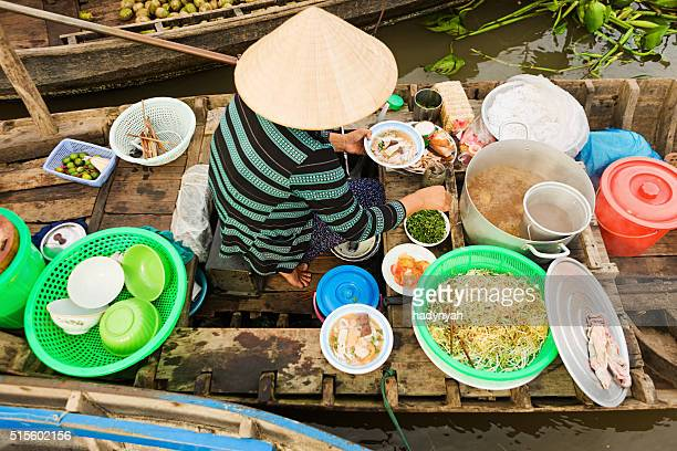 Femme vente Pho vietnamien :  bouillon de nouilles au Marché flottant