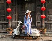 Vietnamese woman sitting on vespa on street side