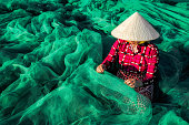 Young Vietnamese woman sitting repair the fish net in the morning,traditional fisherman.