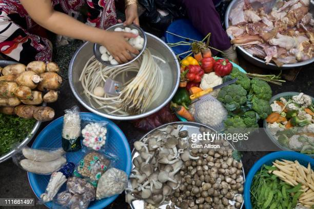 Vietnamese woman sitting with vegetables