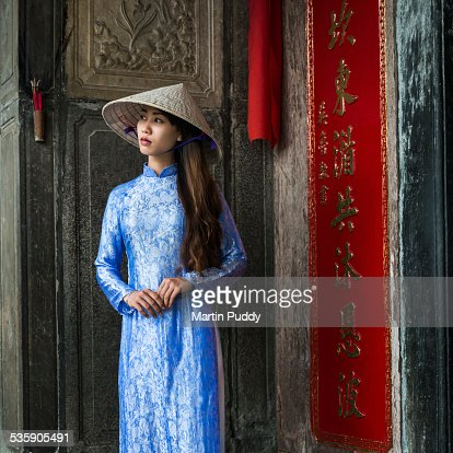 Vietnamese woman standing at temple entrance