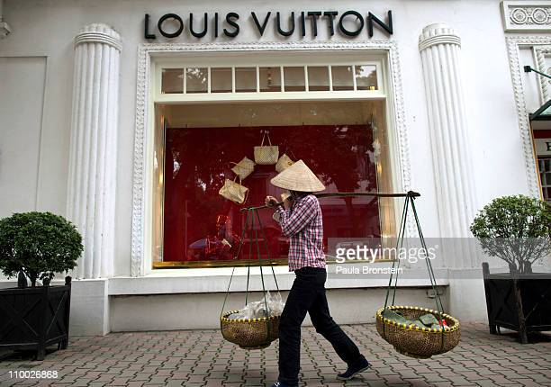 Vietnamese woman walks by the Louis Vuitton shop in the French quarter March 11 2011 in Hanoi Vietnam Over the past year many luxury brands have...
