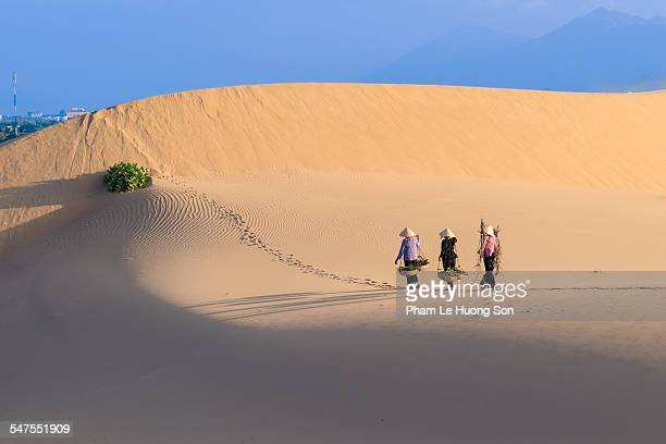 Vietnamese women crossing sand dunes