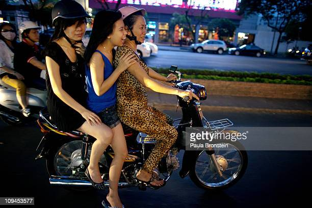 Vietnamese women cruise down the street on a motorcycle February 23 2011 in Ho Chi Minh City Vietnam Over the past year many luxury brands have...