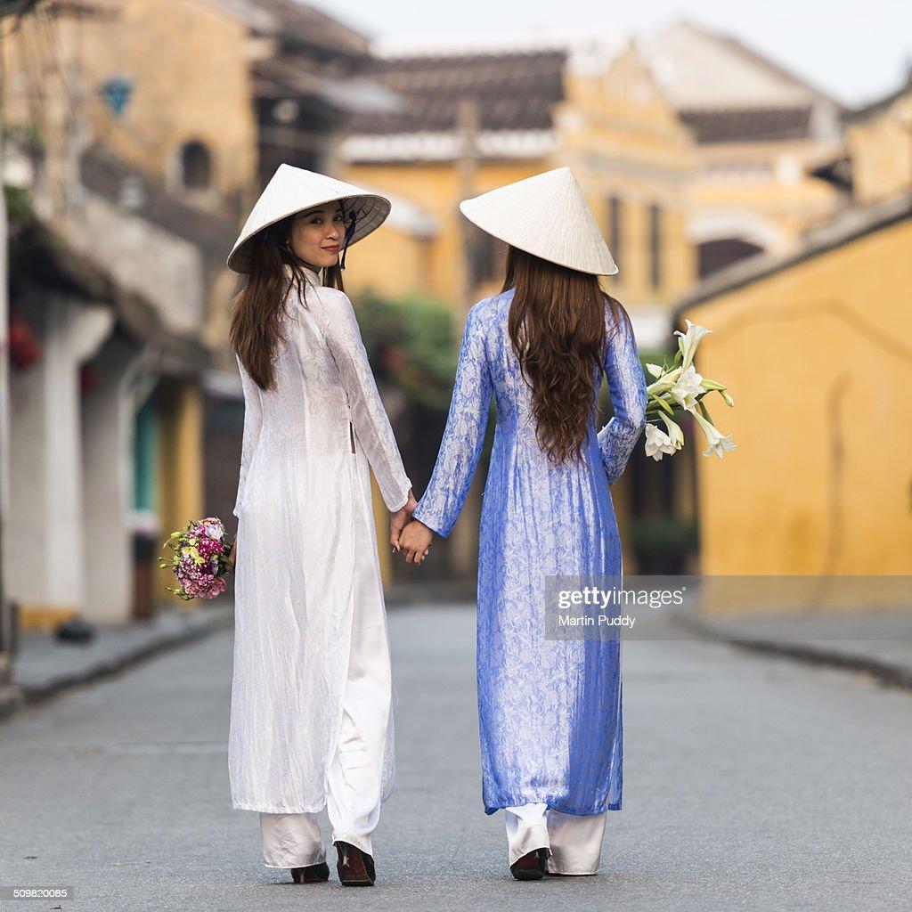 Vietnamese women walking along street