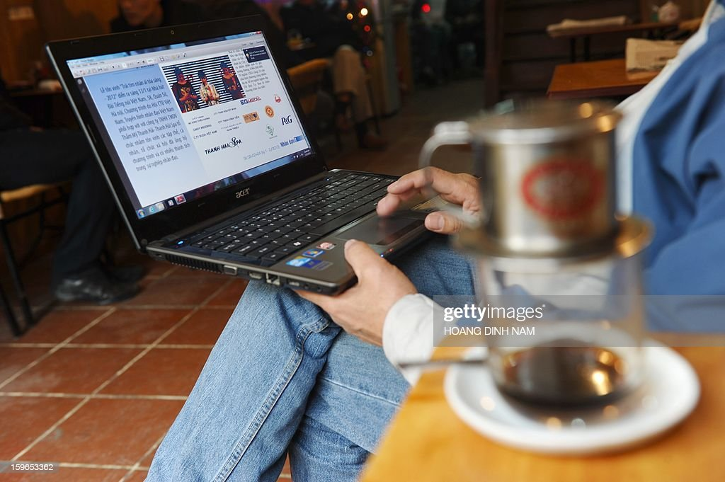 WITH 'Vietnam-politics-internet-censorship,FOCUS' by Cat Barton This picture taken on January 15, 2013 shows a man reading online news with his laptop at a coffee shop in downtown Hanoi. After harassment and prison failed to silence Vietnam's dissident bloggers, the communist government started building an army of propaganda agents to infiltrate chatrooms and sing the regime's praises. AFP PHOTO/HOANG DINH Nam