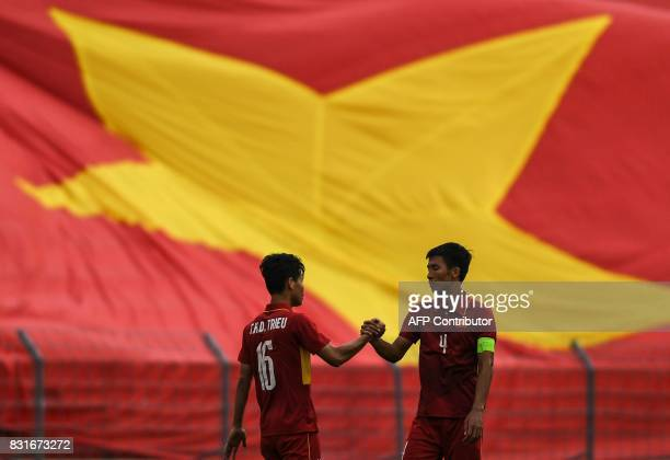 Vietnam's Bui Tien Dung and Tran Huu Dong Trieu shake hands in front of their country's flag after their winning their men's football Group B round...