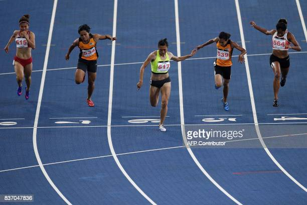 Vietnam's Le Tu Chinh crosses the finish line first to win the women's 100m athletics final of the 29th Southeast Asian Games at the Bukit Jalil...