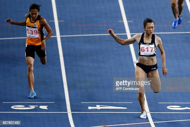 Vietnam's Le Tu Chinh crosses the finish line first to win the women's 200m athletics final of the 29th Southeast Asian Games at the Bukit Jalil...