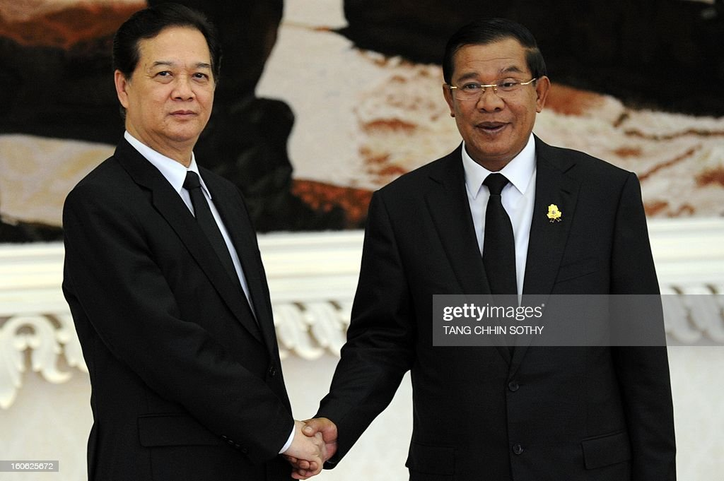 Vietnam's Prime Minister Nguyen Tan Dung (L) shakes hands with Cambodian Prime Minister Hun Sen (R) during their meeting at the Peace Palace in Phnom Penh on February 4, 2013. Dung arrived here to pay his respects and attend the funeral of the late former king Norodom Sihanouk ahead of his cremation on February 4. AFP PHOTO/TANG CHHIN SOTHY