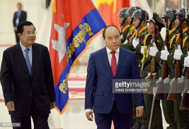 Vietnam's Prime Minister Nguyen Xuan Phuc and Cambodia's Prime Minister Hun Sen walk past honor guard upon arriving at the Peace Palace in Phnom Penh...