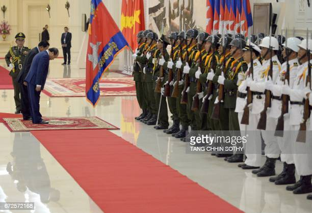 Vietnam's Prime Minister Nguyen Xuan Phuc and Cambodia's Prime Minister Hun Sen pay their respect in front of honor guard upon arriving at the Peace...