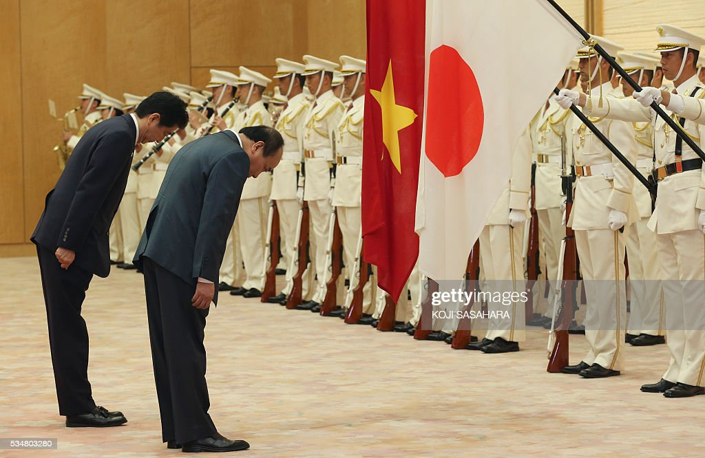Vietnam's Prime Minister Nguyen Xuan Phuc (2nd L) and Japanese Prime Minister Shinzo Abe bow in front of their national flags as they review an honour guard prior to their meeting at Abe's official residence in Tokyo on May 28, 2016. / AFP / POOL / Koji Sasahara