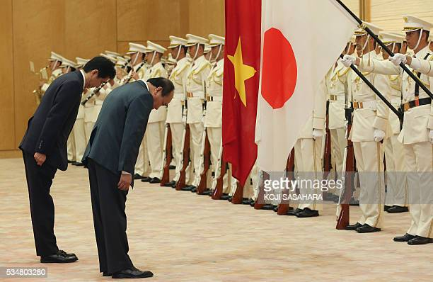 Vietnam's Prime Minister Nguyen Xuan Phuc and Japanese Prime Minister Shinzo Abe bow in front of their national flags as they review an honour guard...