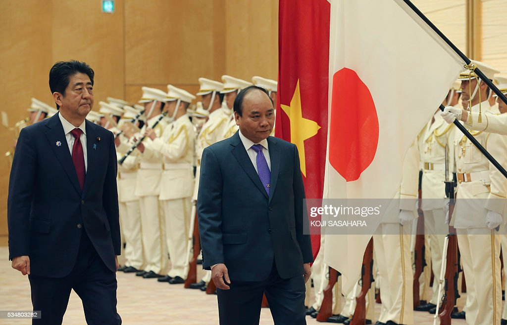 Vietnam's Prime Minister Nguyen Xuan Phuc (2nd L) and Japanese Prime Minister Shinzo Abe review an honour guard prior to their meeting at Abe's official residence in Tokyo on May 28, 2016. / AFP / POOL / Koji Sasahara