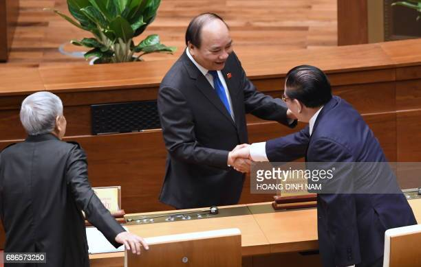 Vietnam's Prime Minister Nguyen Xuan Phuc greets two former Vietnam Communist Secretary Generals Nong Duc Manh and Le Kha Phieu prior to the opening...