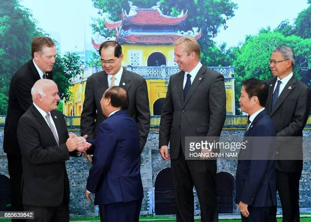 Vietnam's Prime Minister Nguyen Xuan Phuc shakes hands with US Trade Representative Robert Lighthizer as Peru's Foreign Trade Minister Eduardo...