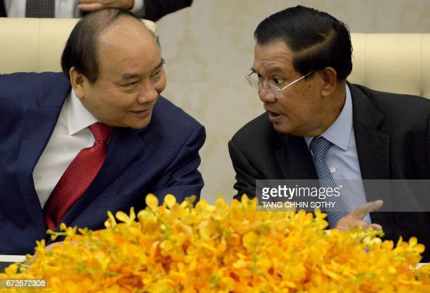 Vietnam's Prime Minister Nguyen Xuan Phuc speaks with Cambodia's Prime Minister Hun Sen during a signing ceremony at the Peace Palace in Phnom Penh...