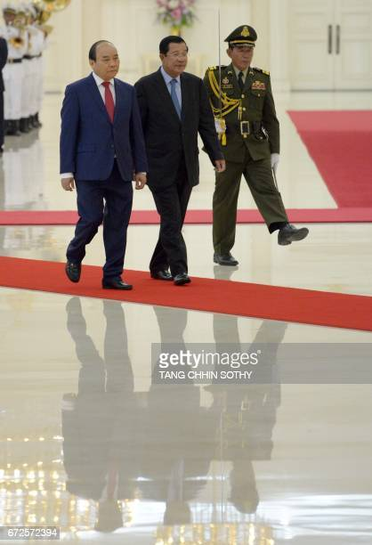 Vietnam's Prime Minister Nguyen Xuan Phuc walks with Cambodia's Prime Minister Hun Sen upon arriving at the Peace Palace in Phnom Penh on April 25...