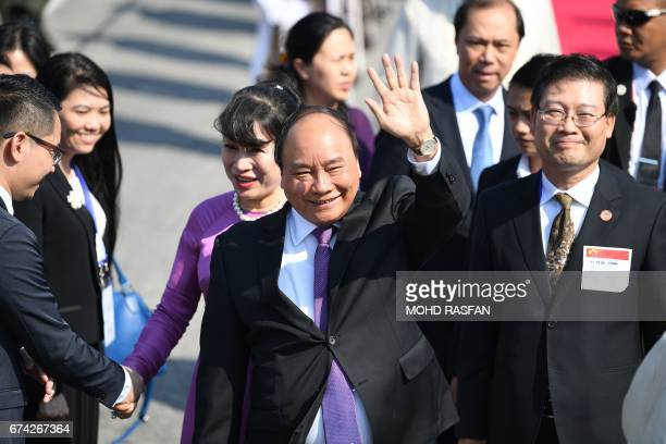 Vietnam's Prime Minister Nguyen Xuan Phuc waves in front of his wife Tran Nguyet Thu as they arrive for the Association of Southeast Asian Nations...