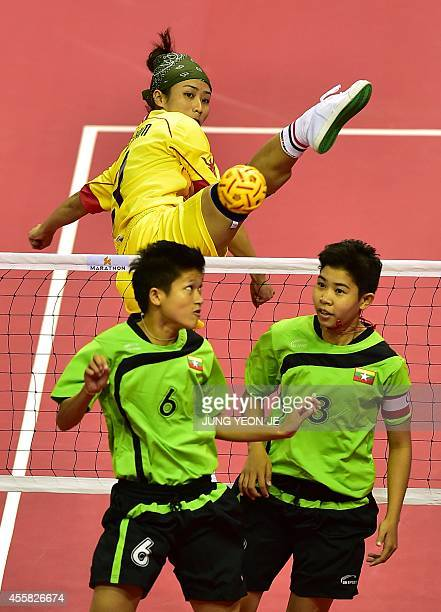 Vietnam's Thi Tam challenges for the ball with Myanmar's Phyu Than Phyu and Kyu Thin Kyu in the women's double preliminary group B sepaktakraw match...