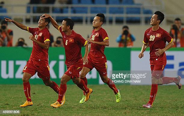 Vietnam's Vu Minh Tuan celebrates with teammates after scoring a goal against Laos during an AFF Suzuki 2014 Cup football match at Hanoi's My Dinh...