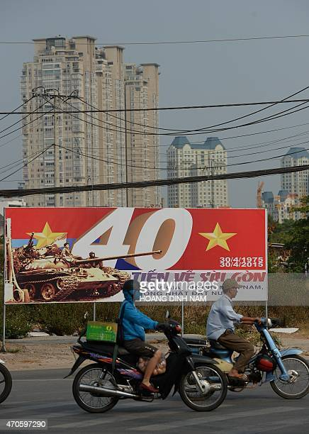 VietnamUSwarmedia FEATURE by Cat Barton This picture taken on April 11 2015 shows motorcyclists riding past a propaganda poster featuring the 40th...