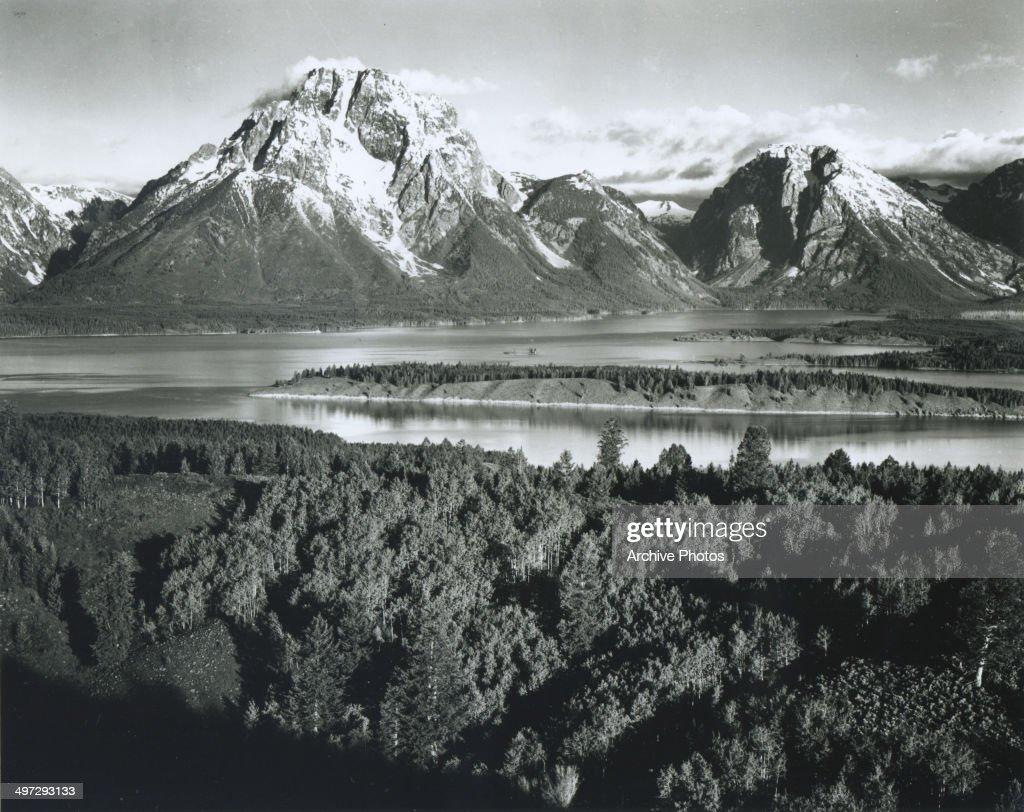 View across a river valley towards Mount Moran in the Teton Range in Grand Teton National Park, Wyoming, 1941.