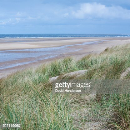View across dunes to deserted beach : Bildbanksbilder