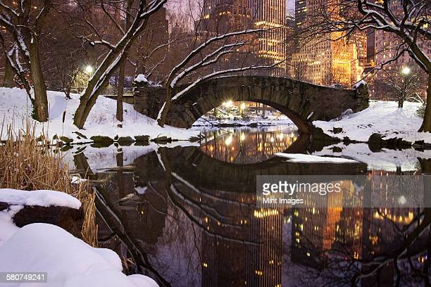 View across the Pond towards Gapstow Bridge in Central Park in Manhattan after a snow storm at dusk.