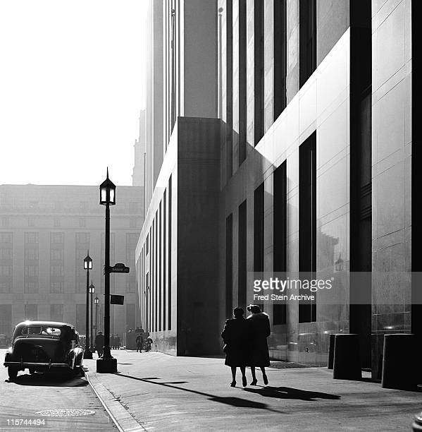 View along Baxter Street at the intersection with Bayard Street where two women walk past the back of the New York Criminal Court Building New York...