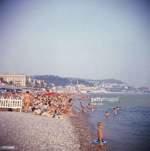 View along the rocky beach crowded with sunbathers and swimmers at Nice France August 1969 The Promenade des Anglais runs along the beach from left