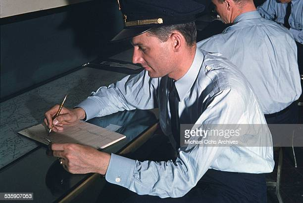 A view as a pilot for American Airlines fills out paperwork