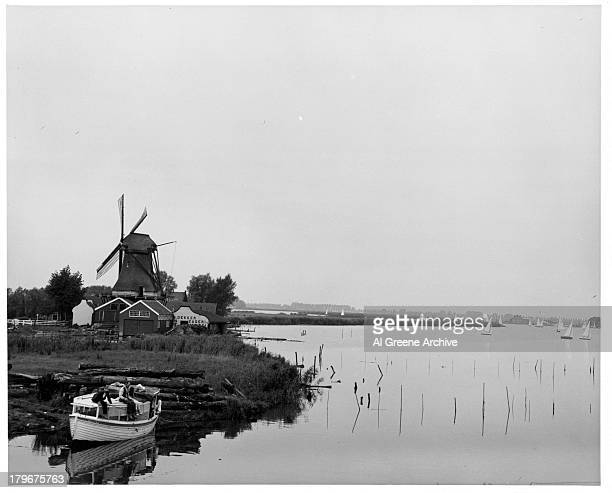 A view as boats sail on the river past windmills in VolendamHolland