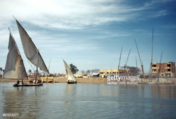A view as men sail a flat bottom sail boat on the Nile river in Aswan Egypt